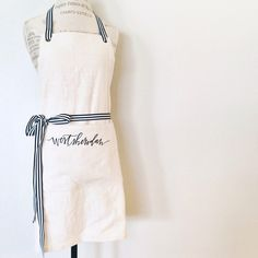 Navy ribbon with the batter and braid logo / custom FULL apron : vendor aprons, custom embroidery, florist apron, event planner apron, photorapher apron, bakery apron by oatmeallacedesign on Etsy https://www.etsy.com/listing/191312301/custom-full-apron-vendor-aprons-custom