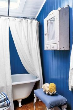 Here the more traditional blue-and-white palette is reversed: The walls become a bold blue while the fixtures and shower curtain remain white. A dark wall color is easier to handle in the bathroom because time spent here is brief. With a chrome shower curtain rod — outfitted with two white terry-cloth curtains — this bath feels like a spa retreat. Click through for more blue and white home design ideas.