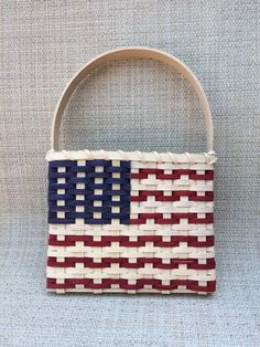 This is a popular basket for Memorial Day, the Fourth of July, Veterans Day, and any time youre feeling patriotic! The flat profile is perfect for hanging on your front door (using a standard wreath hanger) or door knob, and it can be used as an indoor wall hanging or tabletop decoration. One of our state senators recently purchased one to display in her office -- what a compliment! Measures approximately: 8 wide 6.5 high at top of basket 12 high at top of handle 1.5 deep Woven with all n... Nurse Gift Baskets, Best Gift Baskets, Holiday Baskets, Plant Basket, Bamboo Basket, Weaving Art, Hand Weaving, Basket Weaving Patterns, Bamboo Crafts