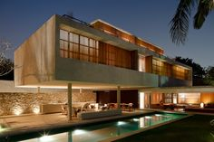 """House 6"": This suave home in Sao Paolo modernizes the traditional Brazilian veranda by placing second story bedrooms above an open television/living room and outdoor kitchen. The stonework and pool blur the edges between interior and exterior space. 
