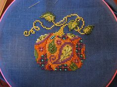 Cute cross stitched/beaded pumpkin. Neat idea to add to cross stitching!  You could mix two patterns to create this look! A background and a silhouette.
