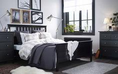 ブラックブラウンのベッドに、ベージュ×ホワイトとダークグレーのベッドテキスタイルを合わせた、広めのベッドルーム。ブラックブラウンのチェストとニッケルメッキ仕上げのランプを配して。