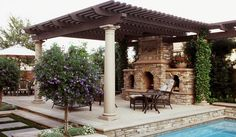tuscan stone outdoor fireplace and poolside outdoor lounge with dark brown rafters