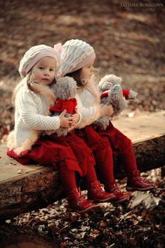 Cute twin girls with their toys in Christmas outfits. #models