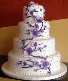 Purple flowers up the side of the cake, like cherry blossoms but not pink