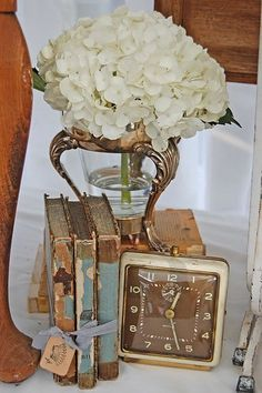 Pretty arrangement of old books, vintage clock and a hydrangea blossom.