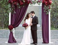 Floral arch with plum drapes and burgundy flowers