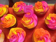 Pink, orange, and yellow tie dye frosted cupcakes.