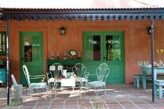 Una casa con estilo campo  Juego de mesa y sillas de hierro (El Galpón) y, detrás de éste, aparador verde comprado en un remate de Ayacucho donde se apoyan los viejos faroles a querosén.