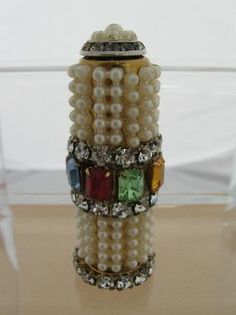 IESNER OF MIAMI Decorated Lipstick w/ Mirror - This is a beautifully decorated Lipstick by the company Wiesner of Miami . The tube cover is decorated with pearls, rhinestones, and multicolored crystal stones. The base has a row of rhinestones around it. On one side of the tube is a beveled mirror. the top of the lipstick case is decorated with pearls and a smaller row of rhinestones.