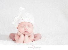 Newborn baby with head in hands