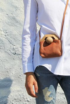 Eatable of Many Orders: Small Tin Bag. Over shoulder leather bag. Sculpted white ash wooden pentagonal handle and ball detail.  Single interior compartment. Cotton and linen blend inner lining. Magnetic snap closure. Made in Japan. http://cdn1.bigcommerce.com/server1900/5b4a5/products/777/images/2057/Tin_Bag_Dark_Brown_Small__41269.1360221944.1200.1200.jpg http://cdn.shopify.com/s/files/1/0066/1582/products/Screen_shot_2013-04-15_at_5.40.23_PM_1024x1024.jpg?33092