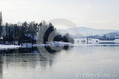 Winter landscape with frozen lake and hills in mirror reflection, located in Moravian Beskydy mountains, part of Czech Republic