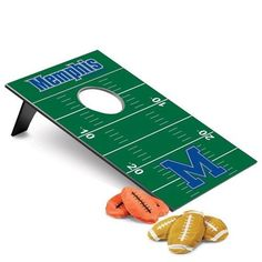 """Memphis Tigers cornhole game. This Tigers bean bag toss game is fun for the whole family. Use indoors or outdoors and play singles or doubles (2 or 4 players). Includes all you need for a day filled with friendly competition! Great for tailgating, parties, the park or beach. Includes: two (18""""L x 28"""" W) game boards, six football-shaped bean bags, and one black polyester carrying tote. All licensed products have been approved by the team; however, Picnic Time is considered a designer line…"""
