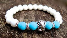 This bracelet was made of tridacna, turquoise, crystals and silver plated elephant bead. It brings strength, prosperity and good fortune.