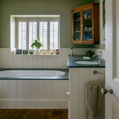 Green country bathroom with wood panelling