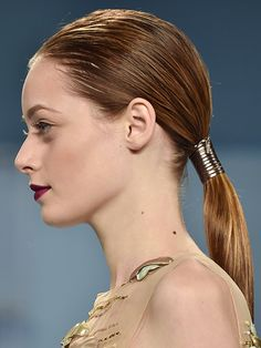 Hair Accessories: a sleek low ponytail wrapped with a strip of leather at Carolina Herrera