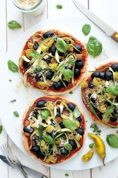 Simple Vegan Pita Pizzas 6 pitas, I used whole-wheat pitas For the tomato sauce 2 large tomatoes, diced 4 sun-dried tomatoes 3 tbsp tomato puree 1 tbsp apple cider vinegar 1,5 tsp maple syrup 2 cloves of garlic 1 large handful of fresh basil 1 tbsp dried oregano 1,5 tsp dried thyme salt, pepper Toppings 1 cup of olives, halved ½ cup of smoked tofu, diced 10-12 pickled peperoncino, sliced ½ zucchini, thinly sliced or shaved 3 tbsp vegan parmesan fresh basil
