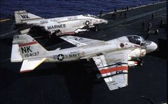 A-6 Intruder from Attack Squadron 196 (VA-196) on the flight deck of the aircraft carrier USS Coral Sea (CV-43). There is also an F-4 Phantom II which is getting ready to launch. The aircraft have Iran Hostage raid markings on their wings.