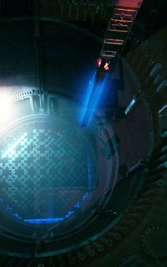 This is a photo of nuclear fuel bundle being lifted from the reactor core. The characteristic blue glow of nuclear reactors is due to Cherenkov radiation or charged particles exceeding the speed of light in a medium.