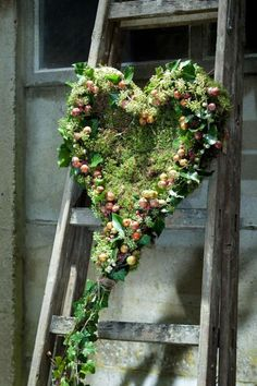 Groen bloemstuk-krans in hartvorm in het midden mos, de rand versierd met hedera, appeltjes en bessen