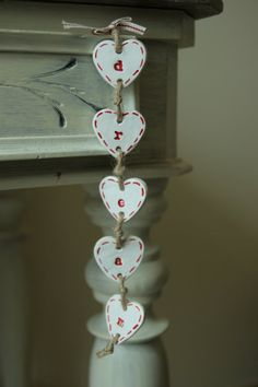 A rustic nordic style decoration with a dream sign which can be customised. The decoration is made out of hanging hearts on a jute twine and an
