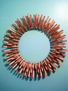 Clothespin Wreath. Made with 1 metal wreath form, 72 (2.75″) clothespins, 72 (3.25″) clothespins, and white spray paint. Might be cool mirror frame too, if you put some plate mirror in the middle. So quirky and fun!