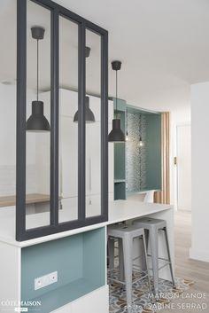 La cuisine ouverte sur le salon offre à voir une belle verrière d'intérieur