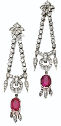 Pair of Art Deco ruby and diamond pendant-earrings, circa 1930. The fleur-de-lis tops supporting diamond-set chains joined by bars suspending circles and fringes, anchored by 2 cushion-shaped rubies weighing approximately 7.00 carats, the whole further set with old European-cut, single-cut, square-cut and marquise-shaped diamonds weighing approximately 5.75 carats, mounted in platinum. #ArtDeco #Earrings