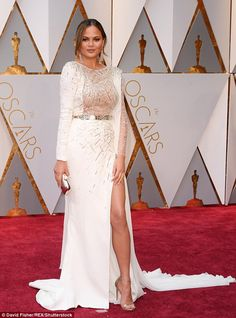Best dressed: Chrissy Teigen stunned in a white Zuhair Murad floor-length gown with a sky-high thigh split that put her famous pins on display at the 89th Academy Awards