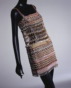"""Dress, Yves Saint Laurent: spring/summer 1967, silk organdy base embroidered with metallic threads, beads, wooden beads and rhinestones, mesh-like beading without backing at waist. """"This dress, presented as one of the 'African Look' collection, fascinated people...This dress is elaborately embroidered with 20 types of beads including sea shells, wooden beads, and animal-teeth-shaped beads, which had rarely been used for Haute Couture before..."""""""