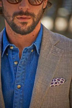 A noter le contraste défini par la chemise en denim et le blazer gris chiné. Cette allure générale est appuyée par l'ouverture des boutons de la chemise qui renforce cet aspect flegmatique. La pochette apporte une touche Preppy qui suit la ligne directrice de la tenue. #modehomme #streetstyle #inspiration #denim #blazer #sunglasses #casual