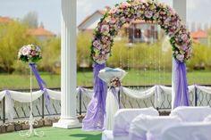 eje de la boda con un arco de flores y sillas blancas