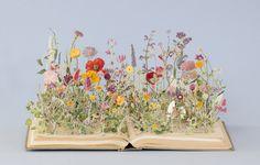 ページの上に美しく咲き誇る色とりどりのお花たち。 まるで物語の世界が目の前に溢れ出してくるようです。 実はこのお花たちは、すべて読み終えた本から生み出された「紙の彫刻」