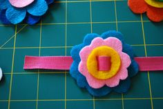 Felt flower bracelets with pattern. Use velcro plant ties for the bands and cut felt for the flowers.  Cut a slit a titch wider than the band into the felt flowers.