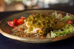 """8 quintessential New Mexican foods Stuffed sopapilla """"Sopapillas are cut squares or triangles of dough, deep-fried until they puff up into hollow little pillows. In New Mexico, they're stuffed with just about anything you want to stuff them with — beans, beans and rice, beans and beef, just beef, chicken, carne adovada, or calabacitas. Once stuffed, the sopapilla is smothered in cheese and your choice of red or green chile, or """"Christmas"""" (a little bit of both red and green)."""""""
