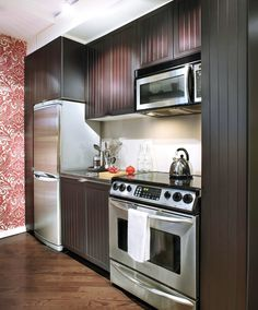 Tiny kitchen with reflective surfaces, dark diagonally installed floors. bachelorette-kitchen.jpg