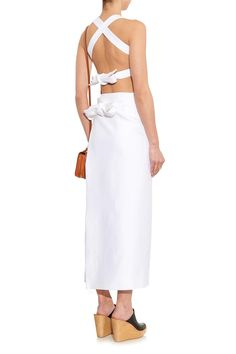 This dress feels understated from the front, but the crossing straps and double bows give it a truly directional feel.   - HarpersBAZAAR.com