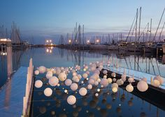 An undulating canopy of lights was strung between two docks to create this installation at a French harbour.