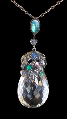 Amy Sandheim (attrib.). Arts and Crafts pendant.  Silver, crystal, moonstone, chalcedony, c. 1930. Pendant: H: 8.5 cm (3.35 in), W: 3 cm (1.18 in). Chain: L: 101 cm (39.76 in). Front view. This is very similar to a pendant by Sibyl Dunlop (see my board for her). I think all three are by the same artist: the fitting around the moonstone on the chain and the facetted small rock crystal below as well as the large facetted rock crystal are all the same; the treatments are all very similar.