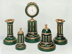 Fabergé Desk Set in Louis XVI Style – An eleven piece set of office desk objects in green jade with gold and gilded gold decoration comprising stand clock, ink vessel, stamp container, bell, ink blotter, pen holder, pen, pencil, table clock, glue pot and two candle holders. Objects made in the Wigström workshop