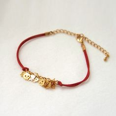 Baby Skull Bracelet -gold plated brass in red cord. $14.00, via Etsy.