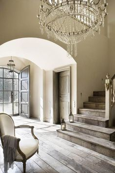 An over-the-top chandelier compensates for an otherwise minimal entryway.   - HarpersBAZAAR.com