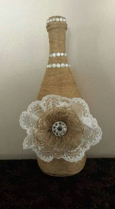 Twine wrapped wine bottle with burlap flower
