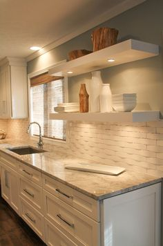 Granite counters with a clean white backsplash?..love the open shelving to display all white serving pieces