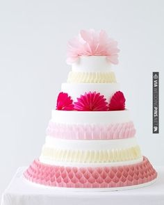 Paper ornaments in bright shades are a style-savvy and budget-friendly way to decorate an all-white cake | VIA #WEDDINGPINS.NET
