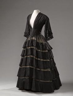 Black muslin dress, 1850-55 – Black wool muslin gown, with flared sleeves, tight fitting bodice and five strips (tiers) on the skirt. The bodice with V-neck runs from the front into a point and is lined