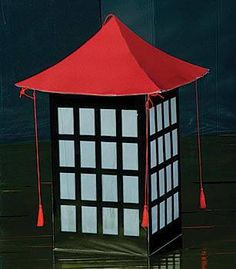 Our Evening in The Orient Lantern features a large Chinese style with a black base, red top and tassel accents. Each Evening in The Orient Lantern measures 3 feet high.