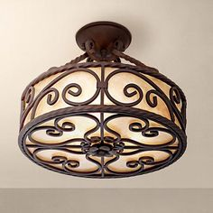 A handsome ceiling light with a deep walnut finish and detailed iron scrollwork.