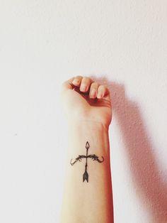 Pequeño tatuaje de una flecha en el antebrazo.